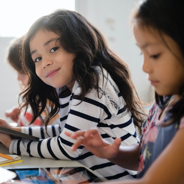 Girl smiling at desk next to peers