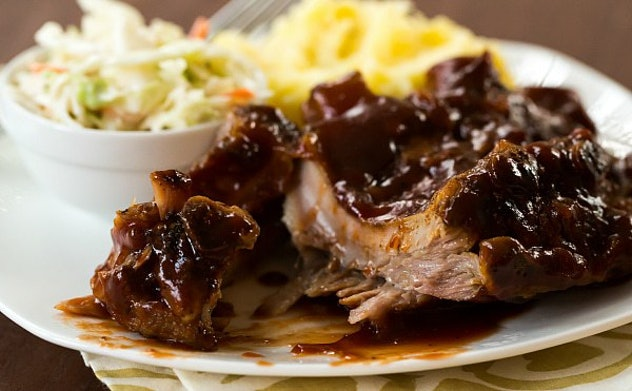BBQ ribs on a white plate with coleslaw and another side dish