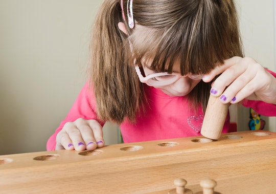 Young girl playing with wooden Montessori blocks