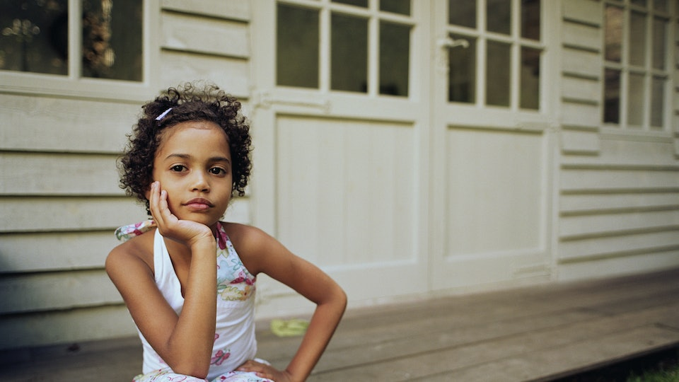 A young girl sits on a porch