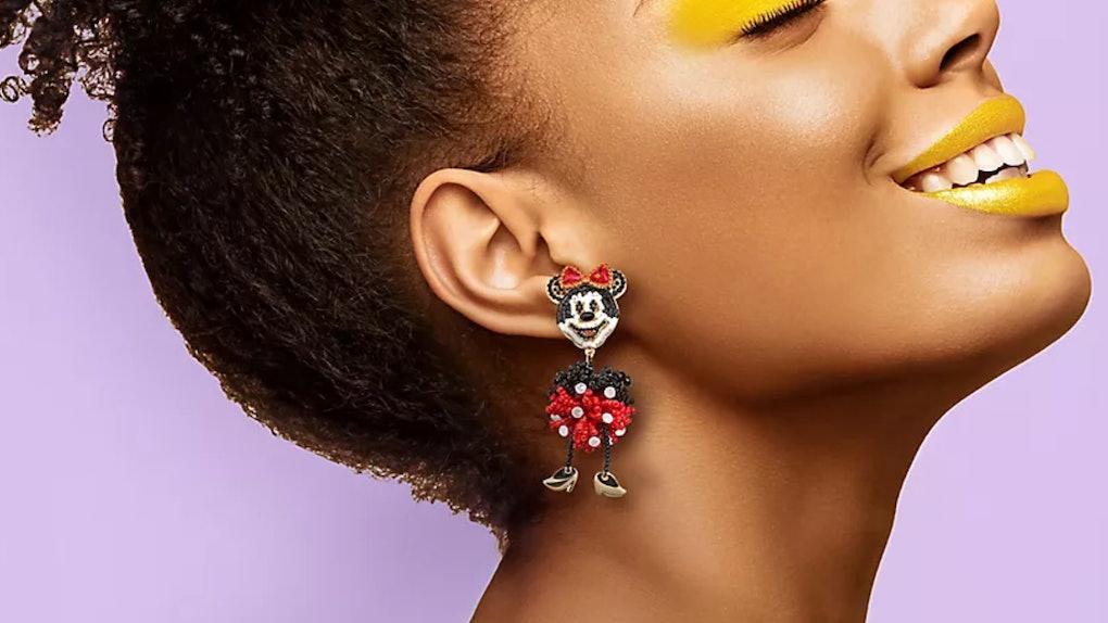 A happy woman wears Minnie Mouse Disney Parks x BaubleBar earrings.