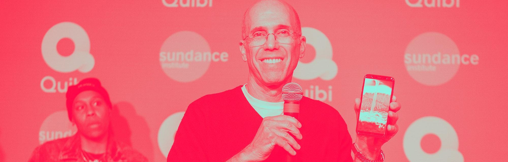 Jeffrey Katzenberg holding up a phone running Quibi.