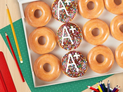 A box of donuts. There are a few plain glazed, a few chocolate filled with an A+ on top, and it's surrounded by school books and colored pencils.