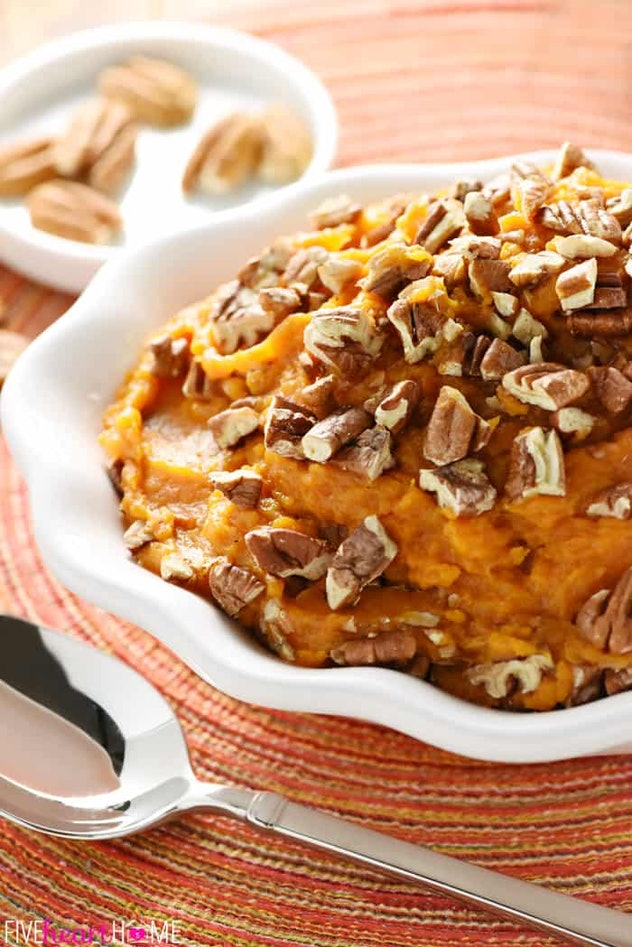 Sweet potato casserole in white bowl placed on top of colorful place mat with a spoon next to it