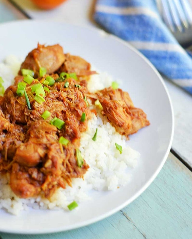 Orange chicken served on top of rice with green garnishes on a white plate