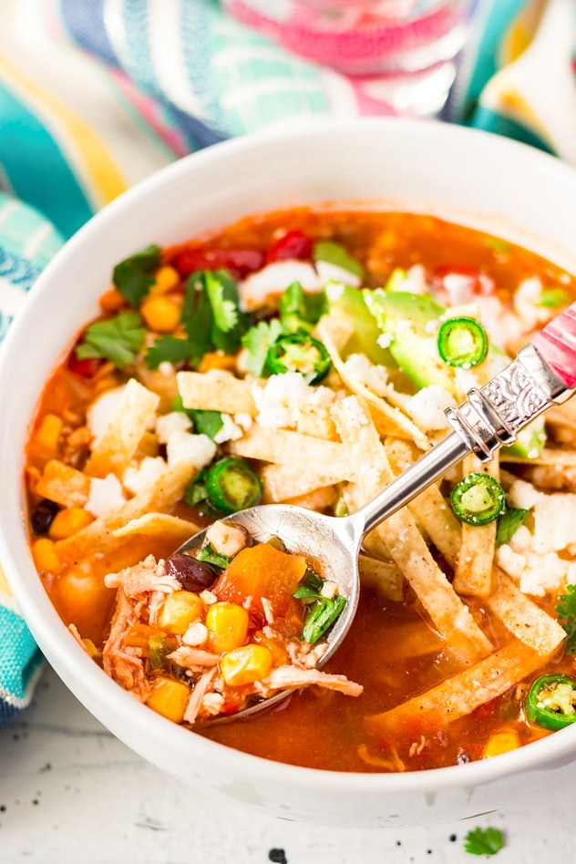 white bowl full of tortilla soup with a spoon coming out of it, holding a spoonful of the soup