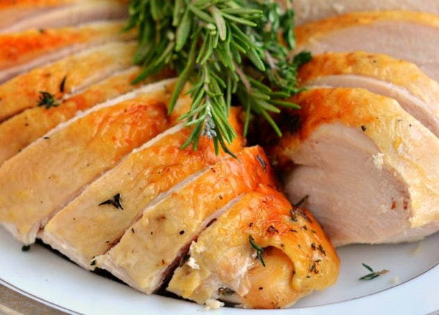 Two slices of turkey breast with herbs and a green garnish on a white plate