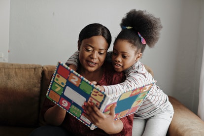 woman reading book to daughter