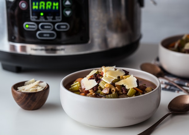 white bowl of minestrone with spoon and small bowl of cheese next to it and a crock pot out of focus in the background