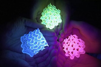 Three pairs of hands can be seen holding bright neon green, blue, and pink fluorescent lights in the dark.