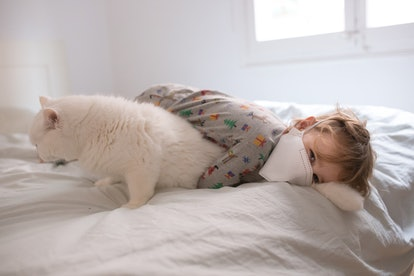 Boy in mask cuddling with cat