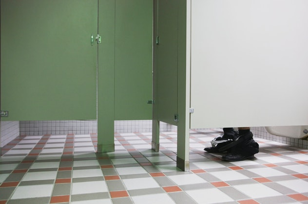 photo of feet visible under public restroom stall