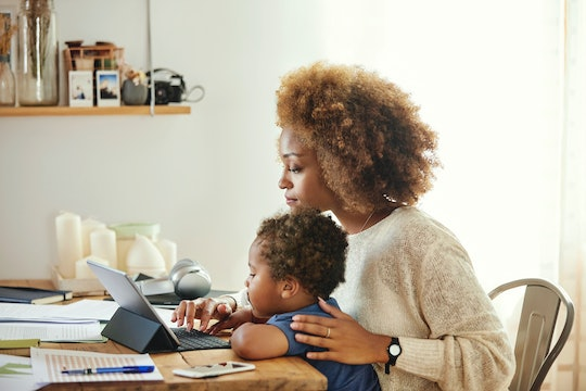 A mother working on laptop with child on lap