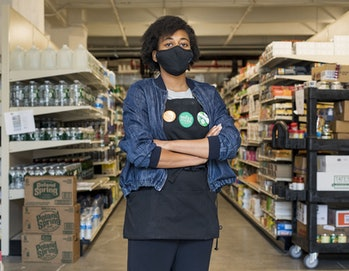 A young worker wearing a blue jacket and black Whole Foods apron is seen with her arms folded. Behind her, there are multiple edible items. She is wearing a face mask.