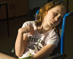 A girl sits in wheelchair with sunlight lighting up her face