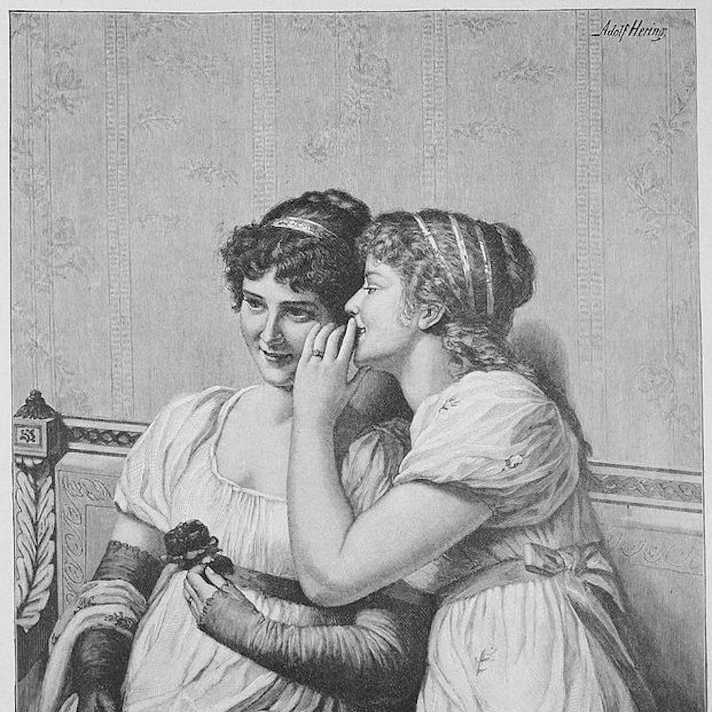 Two girls whisper. Being soft-spoken can help stop the spread of COVID-19.