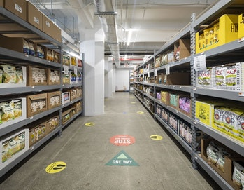 There is an aisle containing multiple shelves of popcorn, chips, and other edible goods. There are no people present in this aisle. The floor presents various direction stickers.