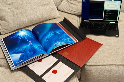 Promotional picture for Disney Codeillusion which features a laptop, the magic book, open to a picture of Elsa from Frozen, and a folder with secret mission envelopes