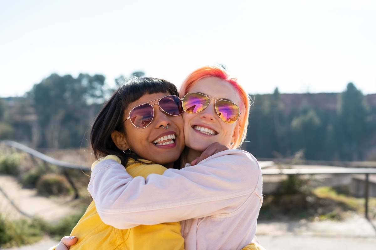 2 young female friends hugging