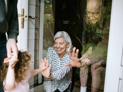 young girl giving grandparents high five through window