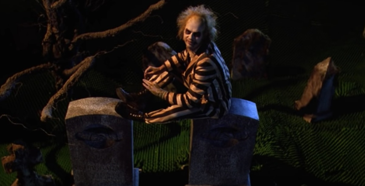 Beetlejuice wears his white and black striped suit and sits on a grave.