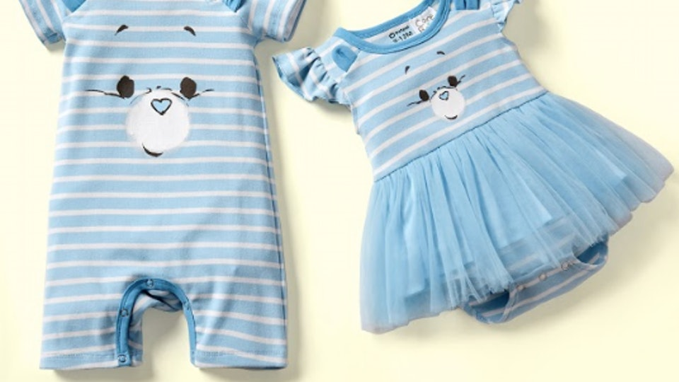 An image of a blue onesie with a Care Bear face on the front and tutu attached beside a larger blue union suit with Care Bear image on the front.