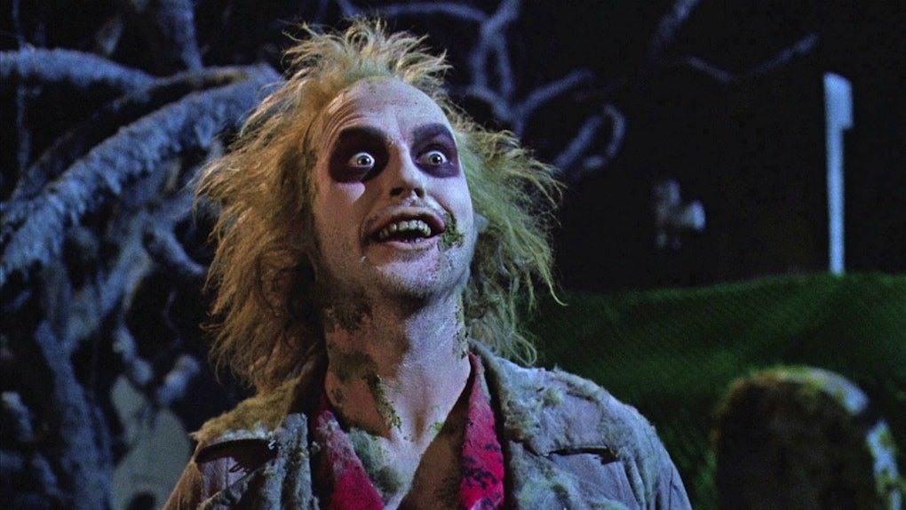 Beetlejuice has dark eye makeup on while he stands in a graveyard.