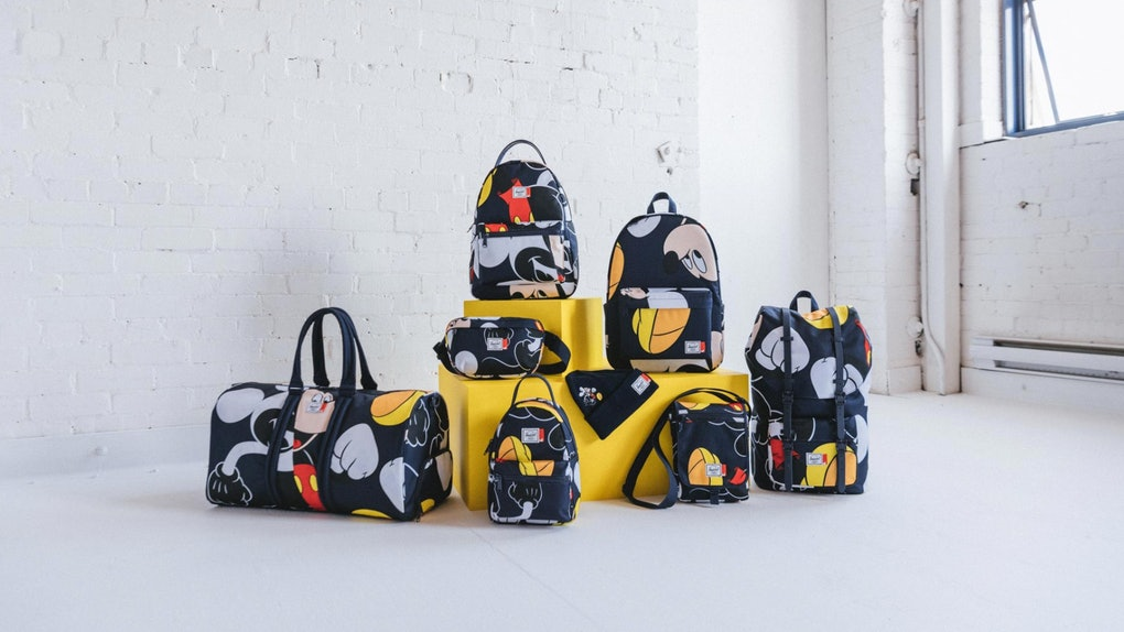 The Herschel x Disney Mickey Mouse collection sits on some yellow blocks in a white loft next to a window.