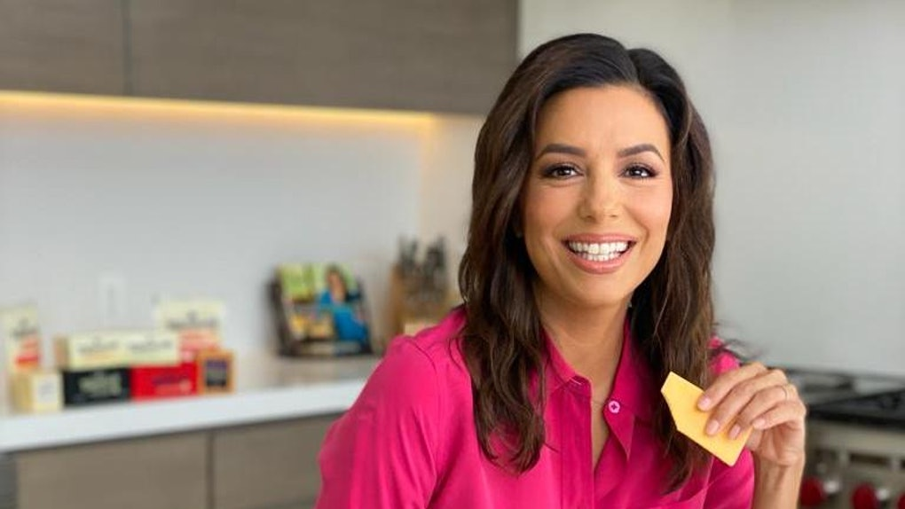 Eva Longoria poses with a piece of cheese while standing in her kitchen.