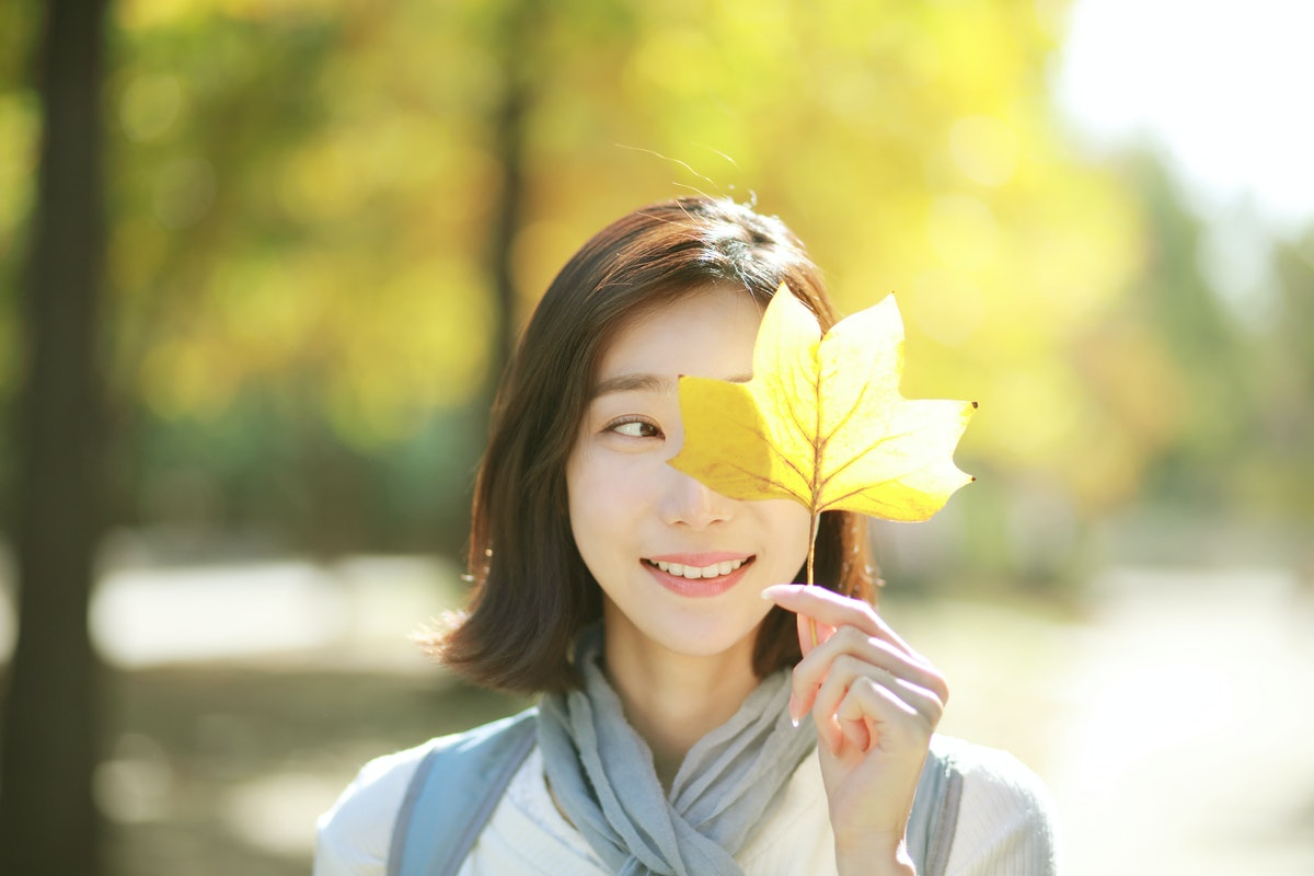 Young woman holding autumn leaf