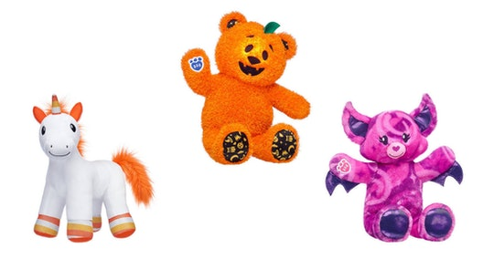 An image of three plush animals. One a bat cat, one a jack o lantern bear, one a candy corn unicorn.