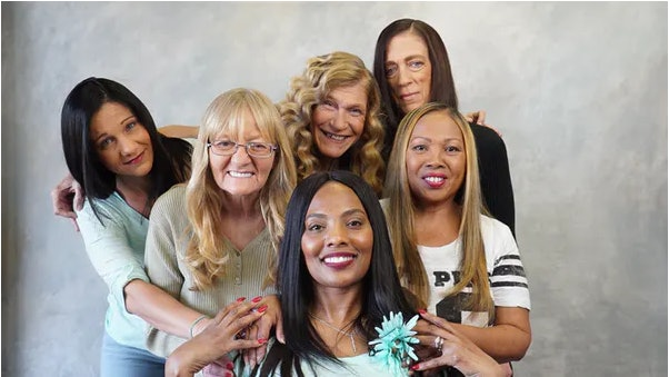 Domestic abuse survivor Vanessa Howard, front, is surrounded by women she helped by giving hair and beauty makeovers in Tampa, Florida, in 2018 to support other women who have experienced domestic violence or homelessness.