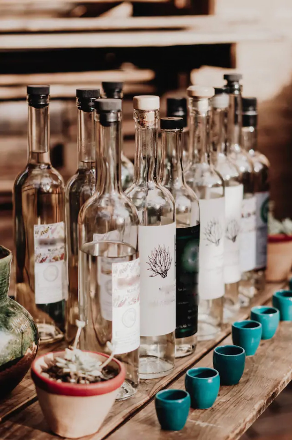 Empty bottles of liquor sit next to bright blue shot glasses on a wooden table.