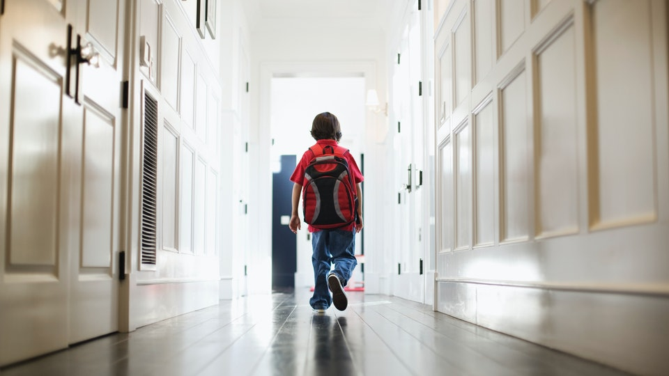 a little boy walking down hall with backpack on way to school