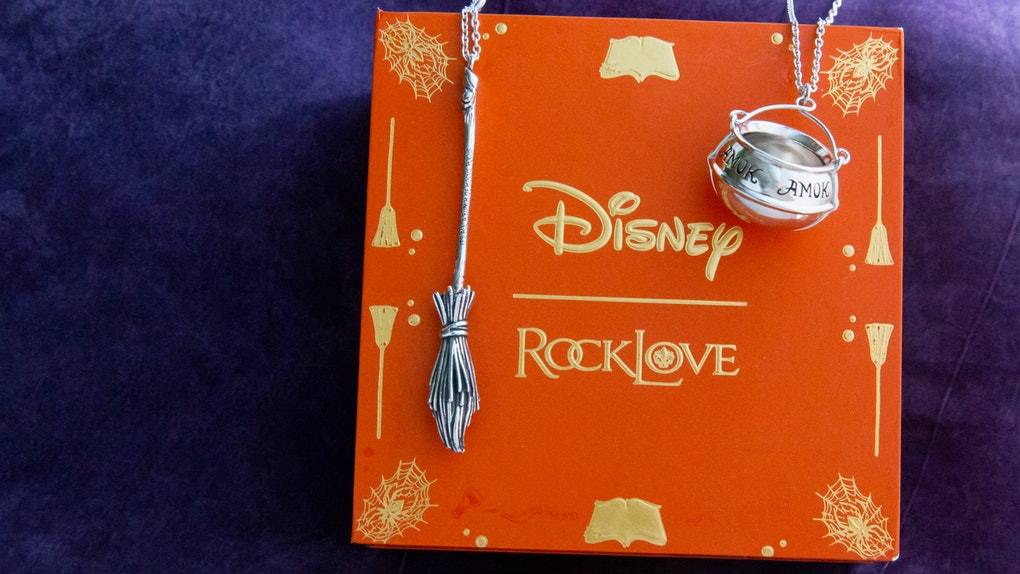 A broomstick and cauldron necklace from the Disney x RockLove 'Hocus Pocus' collection sits on an orange box.