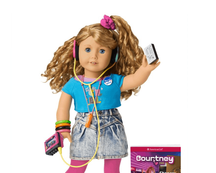 An American Girl named Courtney can be seen with a blue shirt, faded shorts, pink socks, white shoes, and a scrunchie on. She's holding a walkman and wearing headphones.