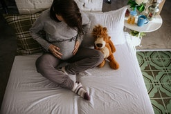 a pregnant woman holding belly on bed