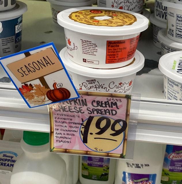 A shelf of pumpkin cream cheese in small tubs.