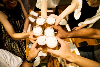 A group of people cheers with pints of beer.