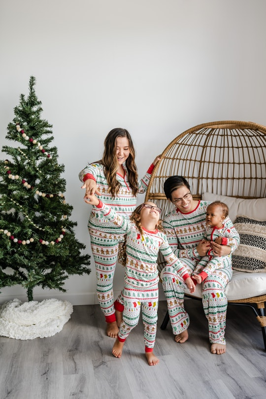 A family in festive long johns in front of a Charlie Brown Christmas tree.