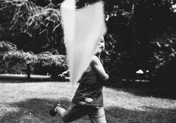 A little boy flies a paper airplane. Black and white photo.