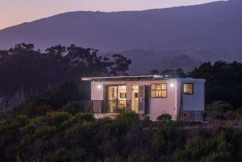 A Living Vehicle trailer home at dusk.