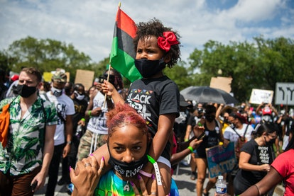 """A little girl rest on her mother's shoulders, as demonstrators walk from the Lincoln Memorial to the Martin Luther King, Jr. Memorial during the """"Get Your Knee Off Our Necks Commitment March on the 57th anniversary of MLKs I Have a Dream speech on Friday, August 28, 2020."""