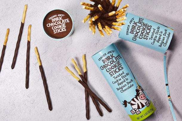 Trader Joe's Dark Chocolate Cookie Sticks are laid out on a concrete table with the canisters they come in.
