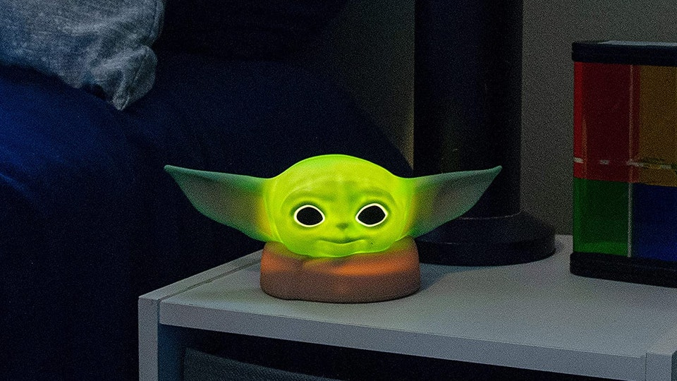 An image of a bed and nightstand with a soft looking Baby Yoda night light glowing atop the nightstand.