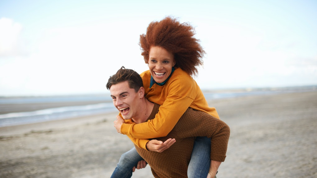 Young couple piggybacking on beach in sweaters