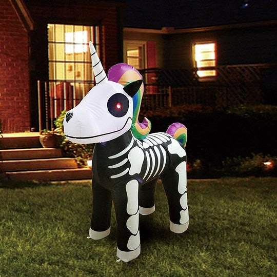 An image of an inflatable unicorn skeleton with a rainbow colored mane and tail in front of a house.
