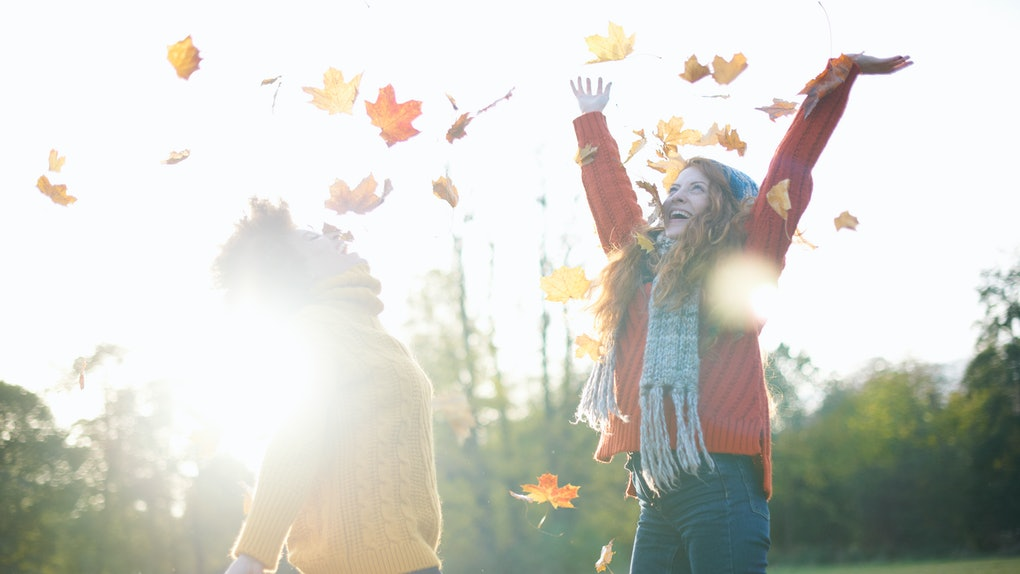 Young women playing in autumn leaves