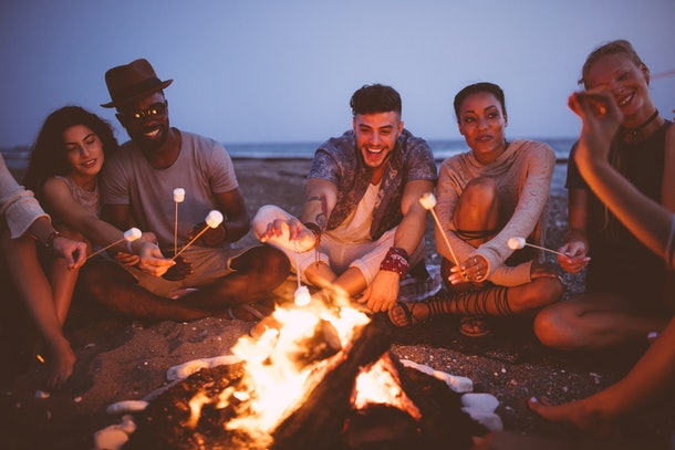 Young people roasting s'mores at beach bonfire