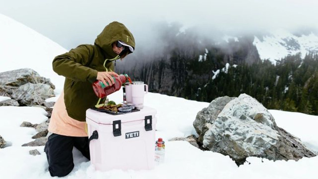 A woman pours a drink in a YETI tumbler on top of a YETI pink cooler.